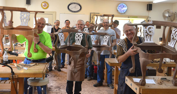 Woodworking students with chairs made at woodworking school