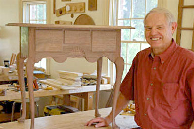 Smiling woodworker with dressing table furniture - our commitment to woodworkers