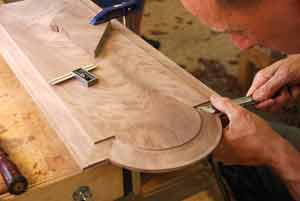 Man carving a frame and panel door